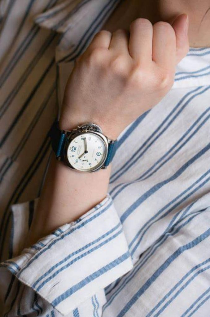 The white dial fake watch has a blue strap.